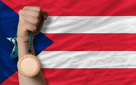 puertorico: Holding bronze medal for sport and national flag of puertorico