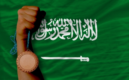 Holding bronze medal for sport and national flag of  saudi arabia photo