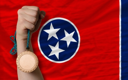 Holding bronze medal for sport and flag of us state of tennessee