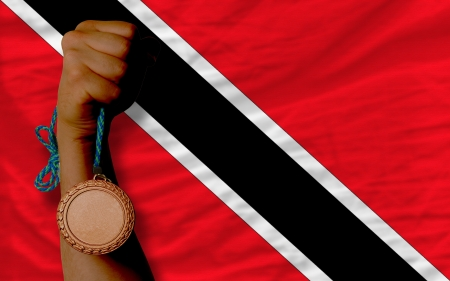 national flag trinidad and tobago: Holding bronze medal for sport and national flag of trinidad tobago Stock Photo