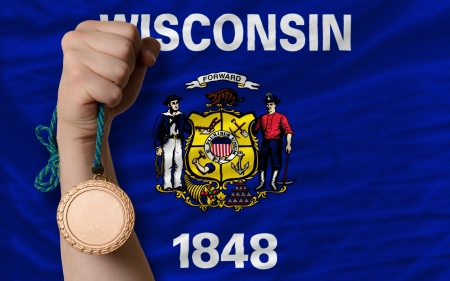 Holding bronze medal for sport and flag of us state of wisconsin Stock Photo