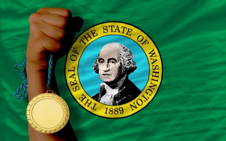 Winner holding gold medal for sport and flag of us state of washington