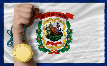 Winner holding gold medal for sport and flag of us state of west virginia photo