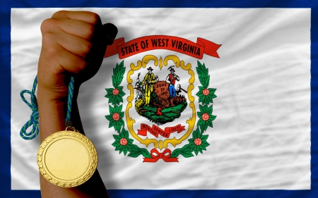 Winner holding gold medal for sport and flag of us state of west virginia