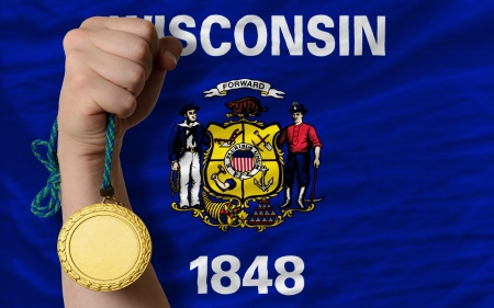 Winner holding gold medal for sport and flag of us state of wisconsin Stock Photo