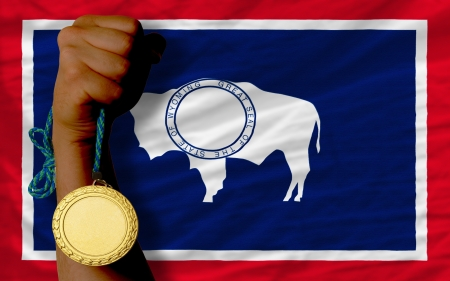 Winner holding gold medal for sport and flag of us state of wyoming