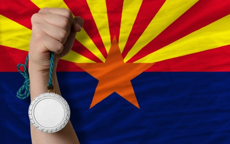 silver state: Holding silver medal for sport and flag of us state of arizona Stock Photo