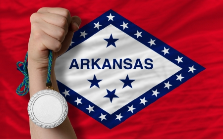 Holding silver medal for sport and flag of us state of arkansas