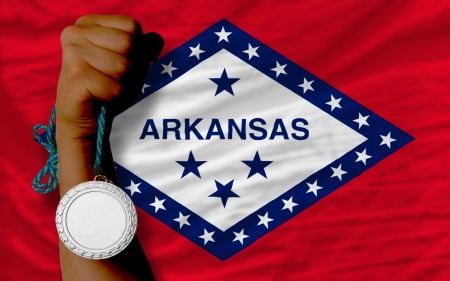 silver state: Holding silver medal for sport and flag of us state of arkansas