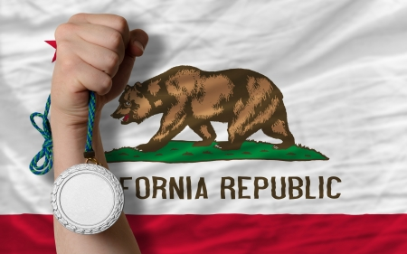 silver state: Holding silver medal for sport and flag of us state of california Stock Photo
