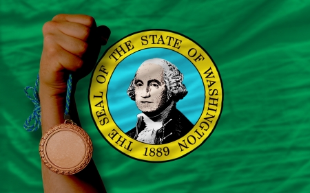 Holding bronze medal for sport and flag of us state of washington
