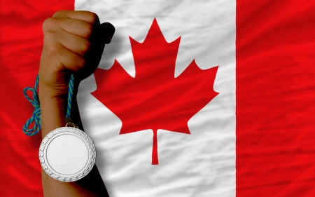 silver medal: Holding silver medal for sport and national flag of canada