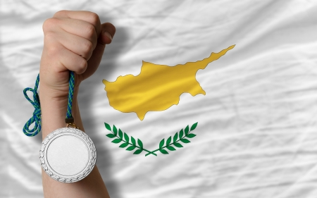 silver state: Holding silver medal for sport and national flag of cyprus