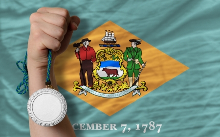 Holding silver medal for sport and flag of us state of delaware Stock Photo