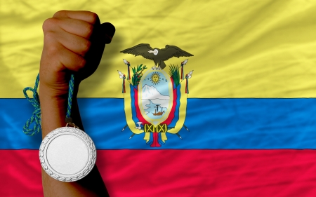 Holding silver medal for sport and national flag of ecuador photo