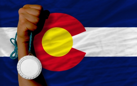 Holding silver medal for sport and flag of us state of colorado