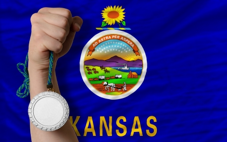 Holding silver medal for sport and flag of us state of kansas