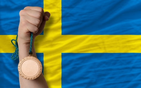 Holding bronze medal for sport and national flag of sweden photo