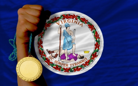 Winner holding gold medal for sport and flag of us state of virginia Stock Photo