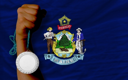 Holding silver medal for sport and flag of us state of maine Stock Photo