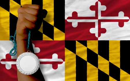 silver state: Holding silver medal for sport and flag of us state of maryland Stock Photo