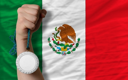 silver medal: Holding silver medal for sport and national flag of mexico