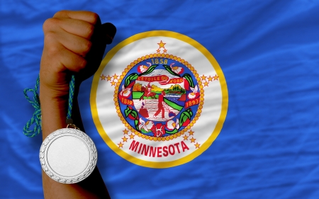 Holding silver medal for sport and flag of us state of minnesota
