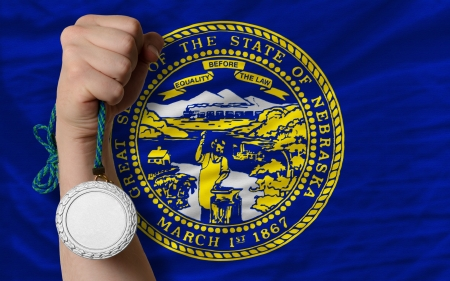 Holding silver medal for sport and flag of us state of nebraska