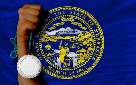 silver state: Holding silver medal for sport and flag of us state of nebraska