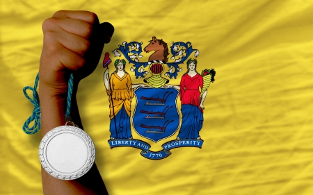 Holding silver medal for sport and flag of us state of new jersey Stock Photo