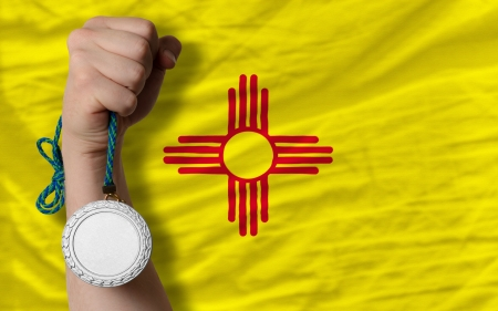 Holding silver medal for sport and flag of us state of new mexico