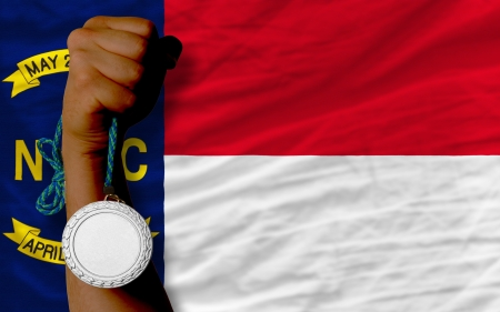 silver state: Holding silver medal for sport and flag of us state of north carolina