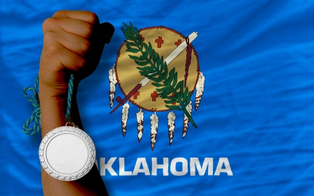 Holding silver medal for sport and flag of us state of oklahoma Stock Photo