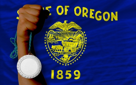 Holding silver medal for sport and flag of us state of oregon