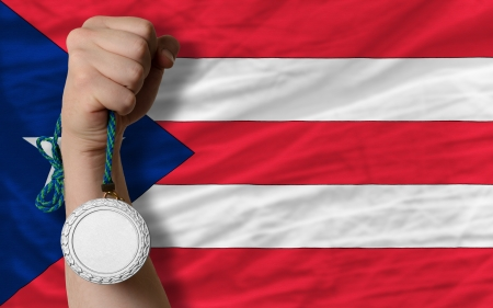 puertorico: Holding silver medal for sport and national flag of puertorico