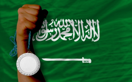 Holding silver medal for sport and national flag of  saudi arabia photo