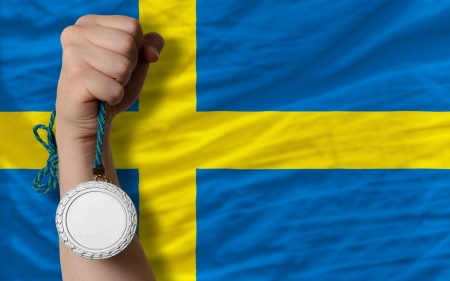 Holding silver medal for sport and national flag of sweden photo