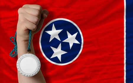 Holding silver medal for sport and flag of us state of tennessee Stock Photo