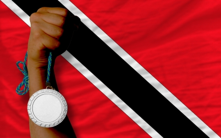 national flag trinidad and tobago: Holding silver medal for sport and national flag of trinidad tobago