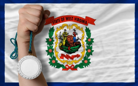 Holding silver medal for sport and flag of us state of west virginia Stock Photo