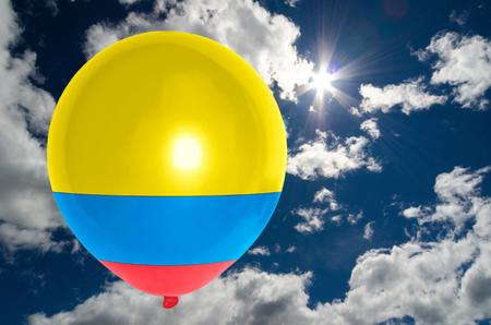 bandera de colombia: balloon in colors of colombia flag flying on blue sky Foto de archivo