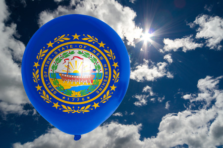nationalistic: balloon in colors of new hampshire flag flying on blue sky
