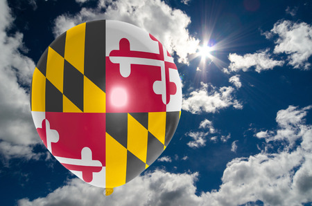 maryland flag: balloon in colors of maryland flag flying on blue sky Stock Photo