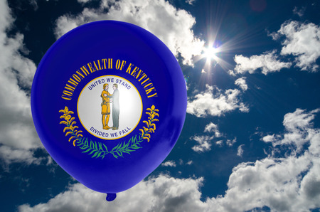nationalistic: balloon in colors of kentucky flag flying on blue sky Stock Photo