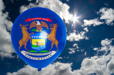 michigan flag: balloon in colors of michigan flag flying on blue sky