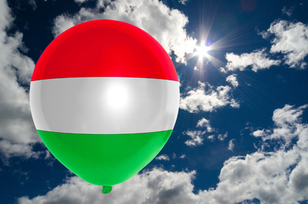 nationalistic: balloon in colors of hungary flag flying on blue sky