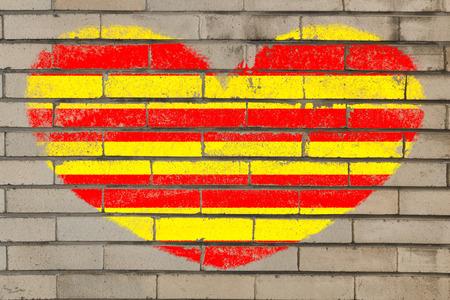 catalonia: heart shaped flag in colors of catalonia on brick wall Stock Photo