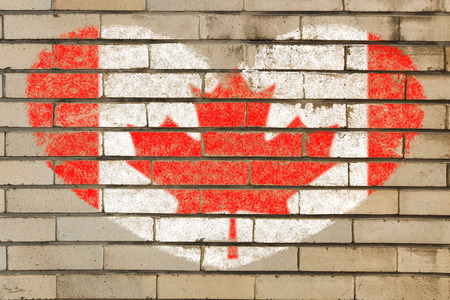 heart shaped flag in colors of Canada on brick wall photo