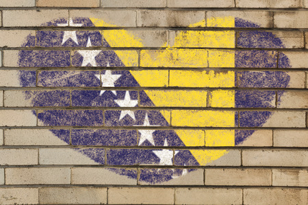 bosnia and herzegovina flag: heart shaped flag in colors of bosnia herzegovina on brick wall