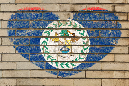 tourism in belize: heart shaped flag in colors of belize on brick wall Stock Photo